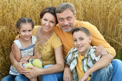 Happy family in wheat field in sunny day