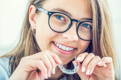 smiling young girl holding ClearCorrect clear aligners