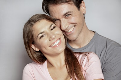 Portrait of an attractive young couple over grey background