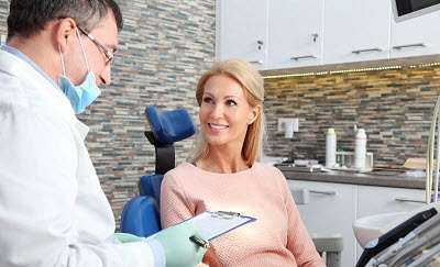 Patient consulting cosmetic treatment options with dentist