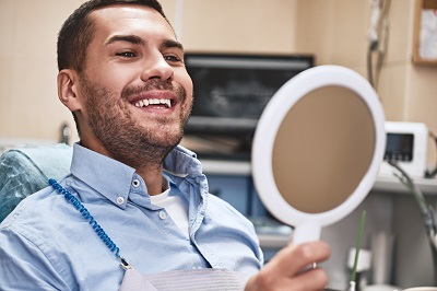 Male patient checking out his smile in dental office after gum contouring treatment