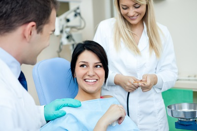 Image of smiling patient sitting in dental chair in dental clinic