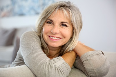Smiling senior woman sitting in couch at home