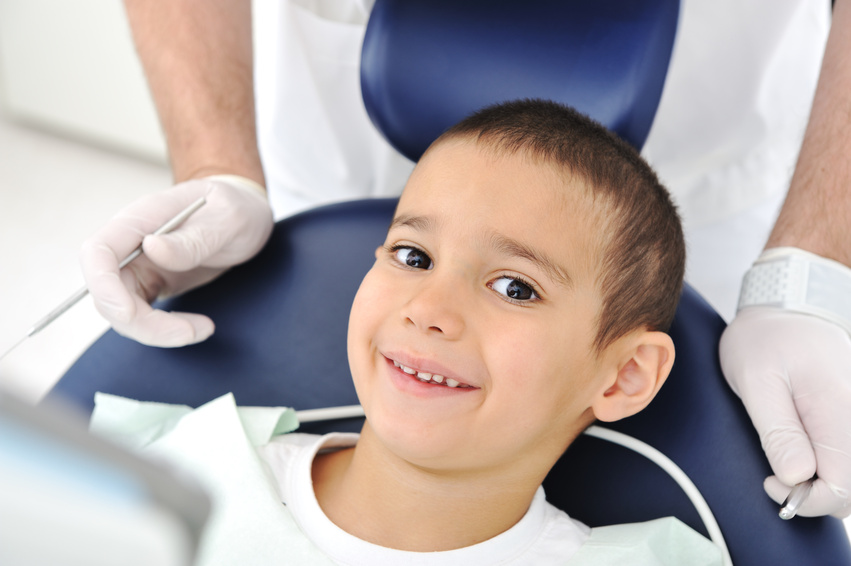 A smiling kid in a dentist's chair having a dental exam by a family dentist.