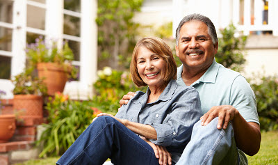 Image of senior Hispanic couple relaxing outside their home