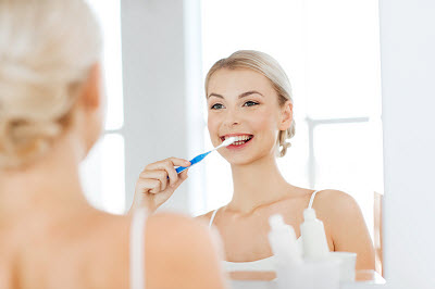 Woman brushing her teeth at home