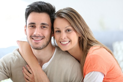 Cheerful couple at home sitting in sofa