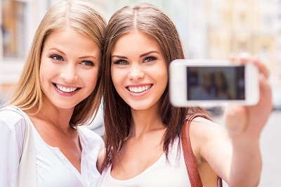 Two attractive young women making selfie and smiling while standing outdoors