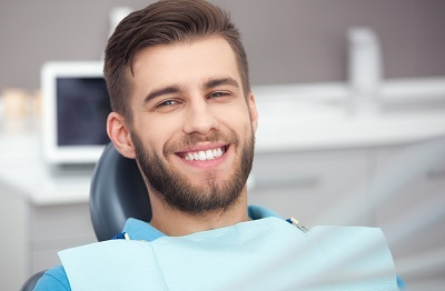 happy male patient sitting in dental chair