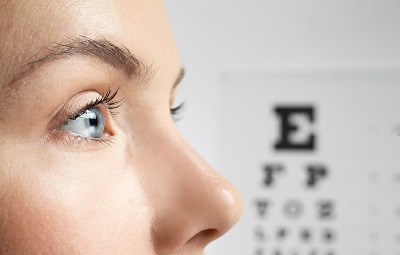 Image of young woman with eyesight test chart background
