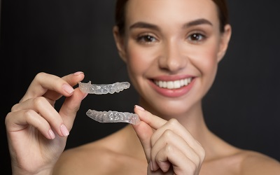 woman holding invisalign clear braces