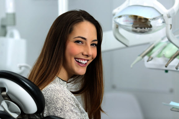 Woman sitting in dental exam chair smiling