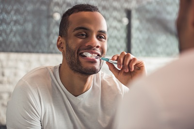 african american man brushing his teeth