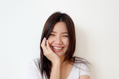 Portrait of a young woman smiling with pink braces