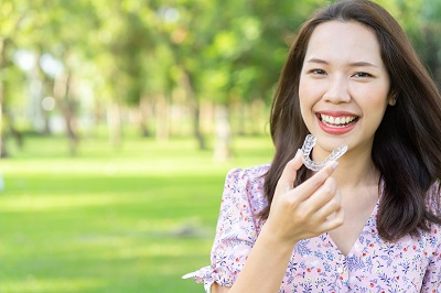 close up young beautiful asian woman smiling with hand holding invisalign clear braces