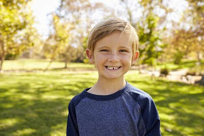 Seven year old Caucasian boy in a park smiling to camera