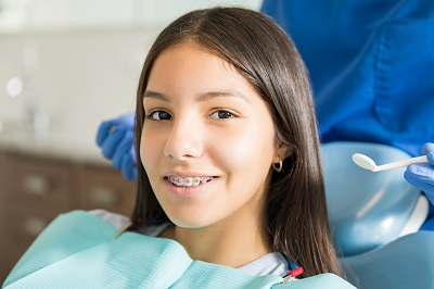 Close-up portrait of smiling teenage girl with braces against dentist standing in clinic