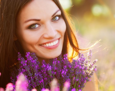 close up of woman with beautiful smile in flower field
