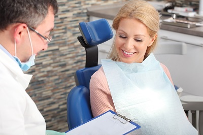 Portrait of beautiful blond woman sitting at dentist office