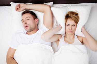 snoring man and angry woman in bed