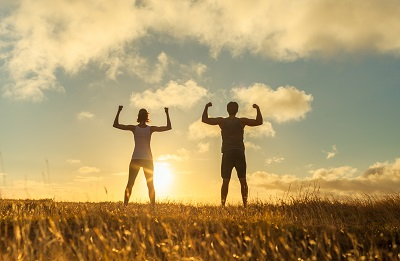 Strong confident man and woman flexing outdoors during sunrise.
