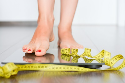 woman standing on weight scale with measuring tape on top