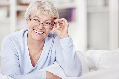 Mature attractive woman with glasses on the sofa
