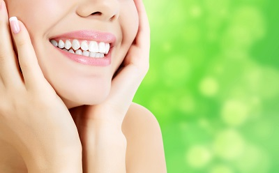 closeup shot of woman smiling with green background