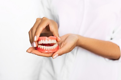woman holding dentures