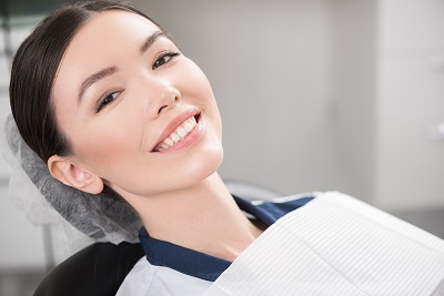 smiling young woman sitting on a dental chair