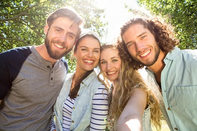 Group of four friends smiling taking a selfie photo at the park.