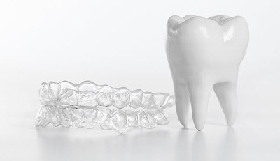 invisalign clear braces next to tooth model