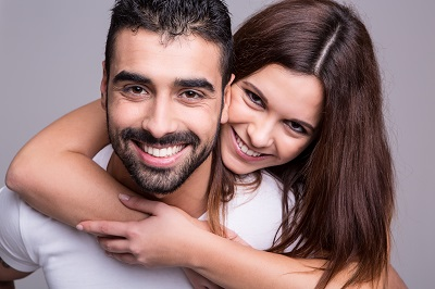 smiling couple over grey background