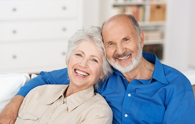 smiling senior couple relaxing at home on sofa