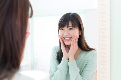 asian woman looking at her smile in home bathroom mirror