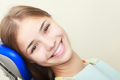 Portrait of female patient smiling while sitting on dental chair