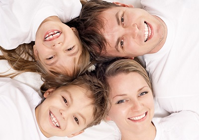 Portrait of a cheerful family having fun together lying on a bed at home