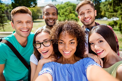 Group of students smiling and taking a selfie together outdoors