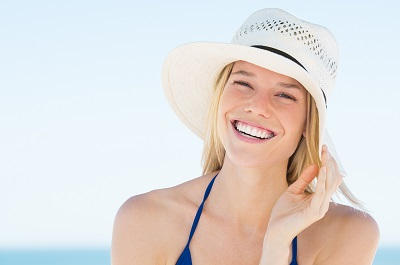 Portrait of smiling woman on beach wearing blue bikini and straw hat.