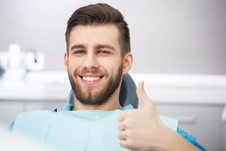 Portrait of happy patient in dental chair making a thumbs up gesture