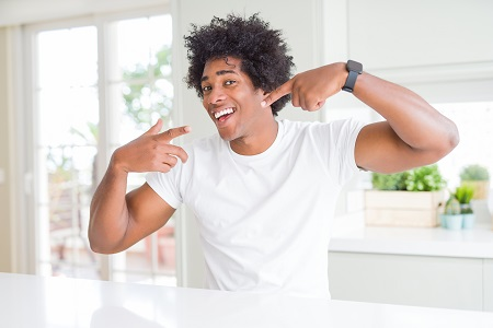 Young african american man wearing casual white t-shirt sitting at home smiling cheerful showing and pointing with fingers teeth and mouth.