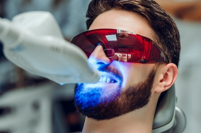 I man sitting in a dental chair getting a zoom teeth whitening procedure.