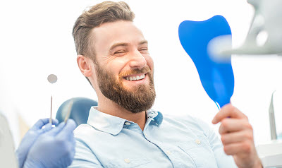 man checking out his smile with a mirror in dental office