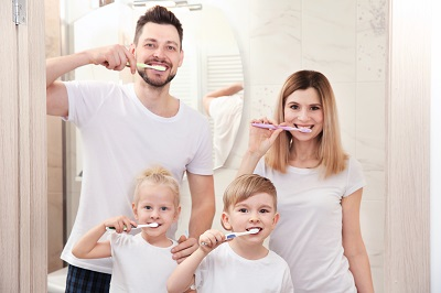 Family brushing teeth together at home