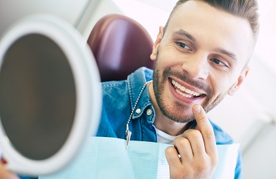 young man checking out his smile with mirror in dental office