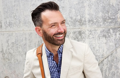 Close up portrait of cheerful middle aged man with beard standing against wall and smiling