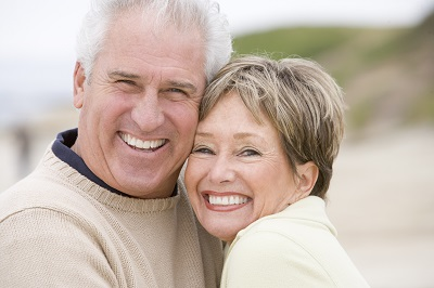 senior couple at the beach smiling
