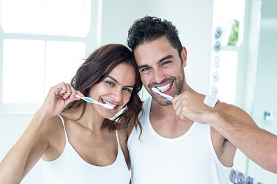 couple brushing teeth at home