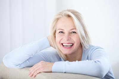 middle aged woman smiling at camera at home