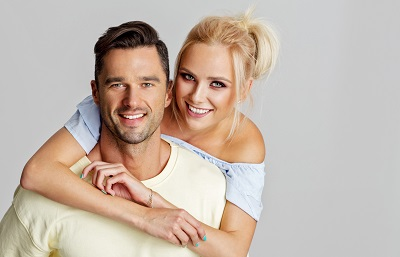 Young adult couple smiling and lookig at camera isolated on gray background